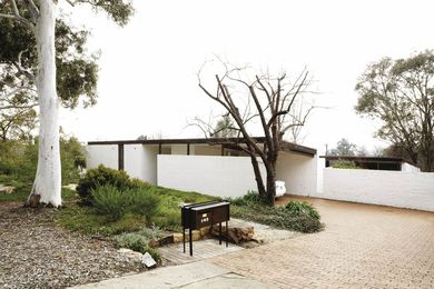 """Arrival to the Cater house. A 1965 newspaper described the house as """"masked"""" and """"introverted,"""" referring to the white wall screening the front of the house."""