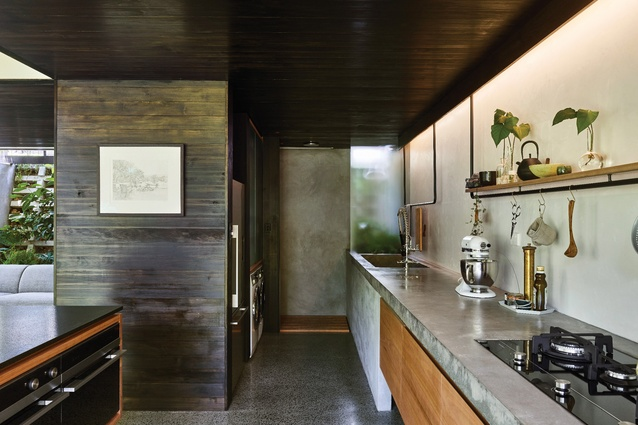 Defined by concrete floors, rendered walls and black-stained timber, the kitchen and living spaces are shadowy and cool. Artwork: Laura Patterson.