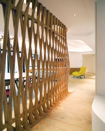 A solid red oak screen, which greets the visitor upon arrival, seeps into the floor via laminate inlaid into a milled plywood subfloor.