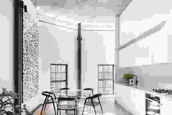 The black and white palette is tempered in the kitchen by a marble splashback and spotted gum timber floors.