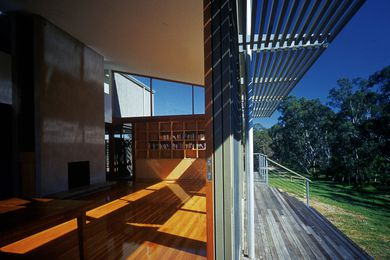 A timber deck steps down towards the river, extending the house into the landscape.