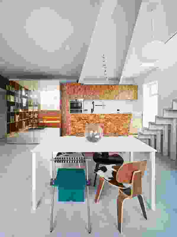 The interior of the apartment is lined with a variety of materials and textures, including oriented strand board seen on the kitchen surfaces.