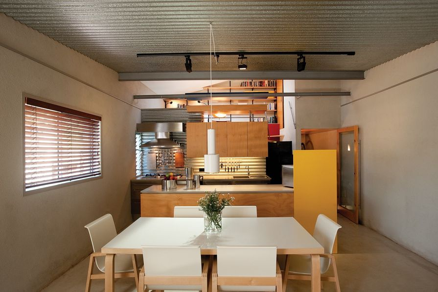 The practical, hoop-pine-clad kitchen lit by concealed downlights.