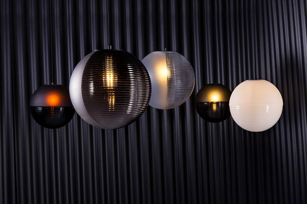 The blown-glass spheres of the Stellar pendant lighting collection for Pulpo are divided into hemispheres of textured and smooth.