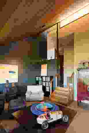 The steep pitch of the ceiling creates dramatic interior volumes. Artwork: Carol Duvall (above fireplace); Makinti Napanangka (above bookshelf); Judi Elliot (glass sculptures on fireplace and coffee table).