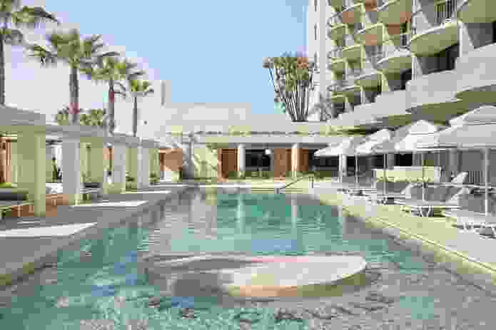 Poolside cabanas and the curved balconies of the hotel rooms above engage guests as both spectacle and spectator.