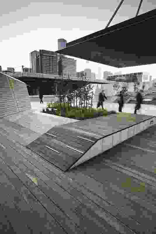 Timber and stone platforms rise out of the ground in the forecourt.