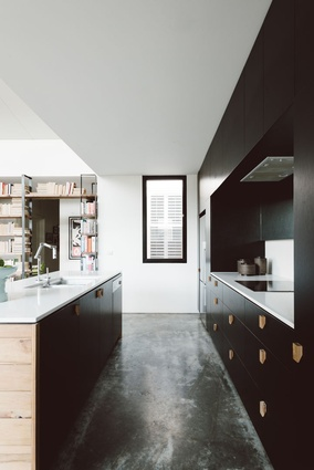 Burnished concrete floors and black cabinetry make for a modern kitchen.