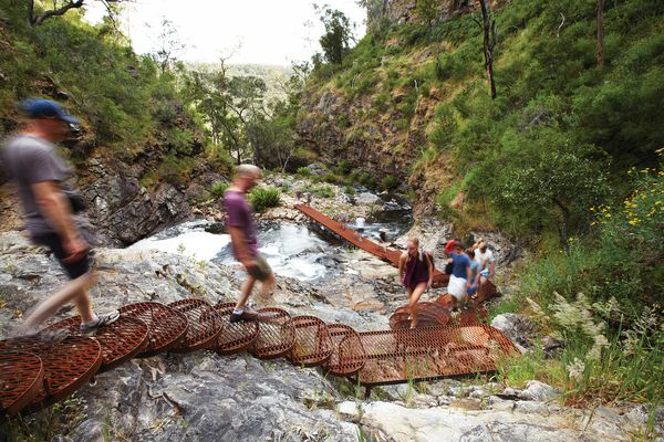 A cascading steel mesh staircase is bolted onto a rock face adjacent to the MacKenzie River.