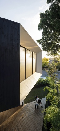 The ground-floor deck provides a quiet, secluded space sheltered by the cantilevered volume's soffit.