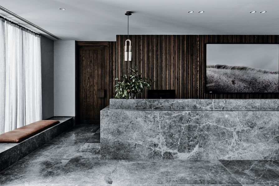 A honed dolomite reception counter appears morphed from the floor.