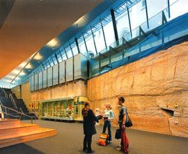 Lower level of the foyer, with the rock wall excavated during construction. Image: John Gollings