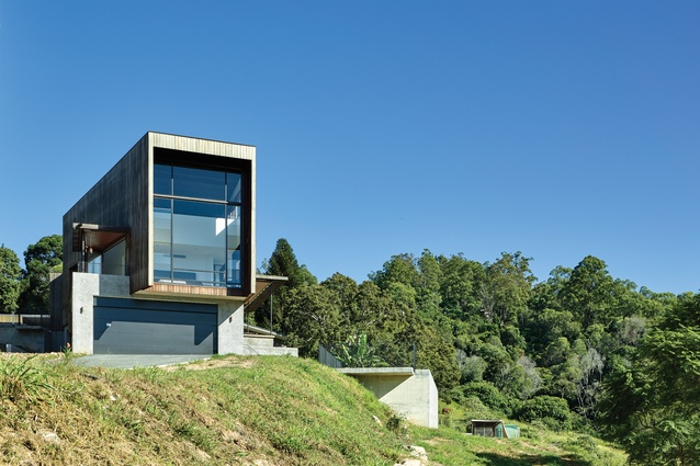 The eastern end of the home lifts to a three-level volume with a giant portal of glazing.