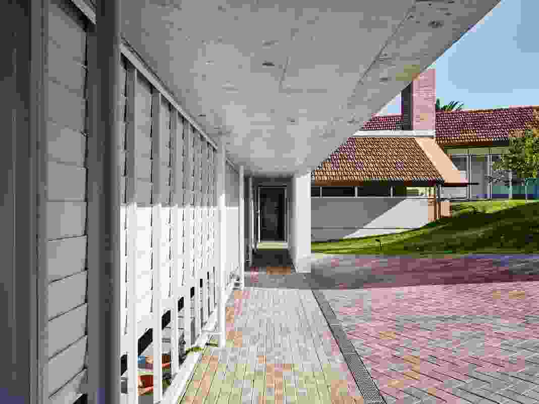 A long entry portico follows the line of a screen that delineates the site into two contrasting topographies of sloped meadow and open field.