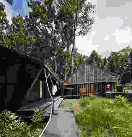 The boardwalk leads from the beach to a series of black pavilions, clad in recycled high-density polyethylene.
