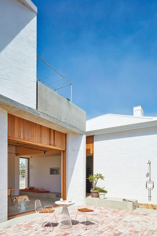 Oversized sliding doors from the living space recede into the wall cavity and open up to a sun-drenched walled courtyard.