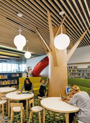On the first level, the children's area evokes the concept of a garden with tree-like columns and grass-green rugs.