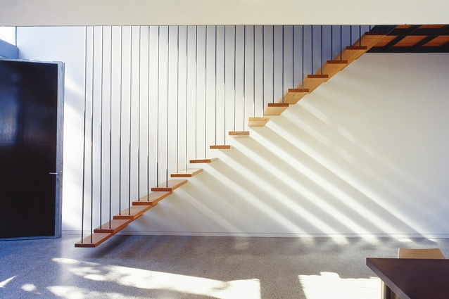 A suspended staircase of floating timber treads maximizes both the real and the perceived space of the ground floor.
