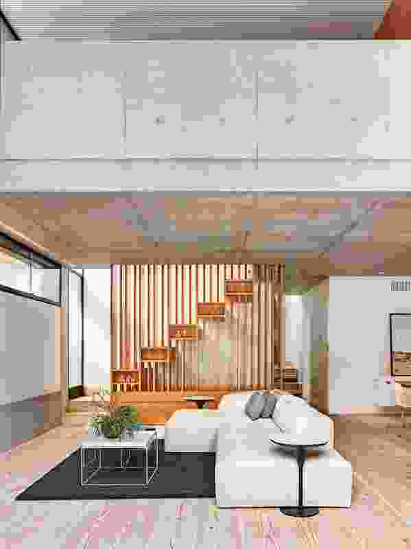 Light filters down from the mezzanine study above the living area through a staircase designed as a series of floating boxes.