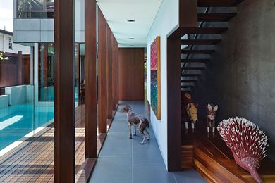 Detailing is a layered, intricate geometric composition of painted plaster and polished timber. Artwork: Michael Johnson (painting); Roderick Yunkaporta (left dog and echidna); Gary Namponan (right dog).