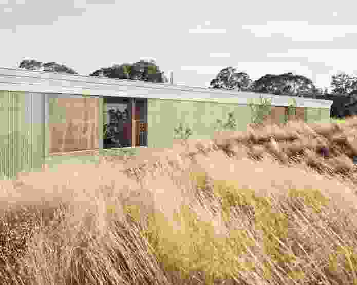 """Sitting low among a series of landscaped berms, the home presents as an industrial shed, its cornice decorated with dots and dashes to spell out """"longhouse"""" in Morse code."""