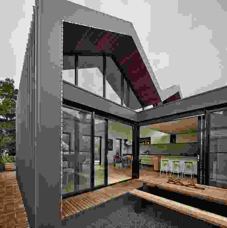 Demolishing the existing lean-to structure, the architect designed a bold new volume to house the kitchen, dining and living spaces.