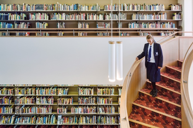 The book collection rooms are two-storey volumes with sweeping stairs that connect the floor levels.