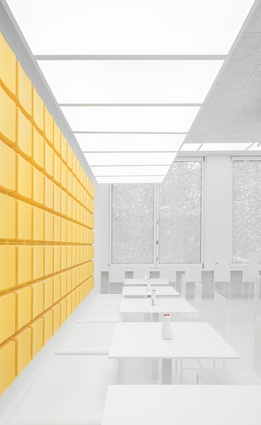 A predominantly white interior acts as a backdrop to a yellow highlight, a signifier of the brand.