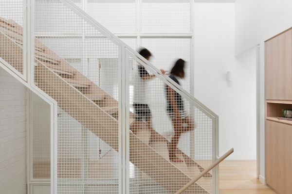 A wire-mesh balustrade provides visual and acoustic connection between levels.