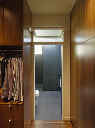 Warm timber lining in the walk-in-robe provides a counterpoint to the cool, dark tones of the tiles in the adjoining ensuite.