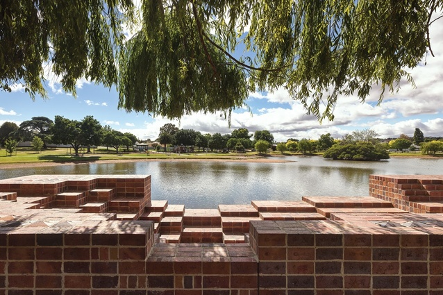 The view is framed by the voids in the brickwork and the willow tree.