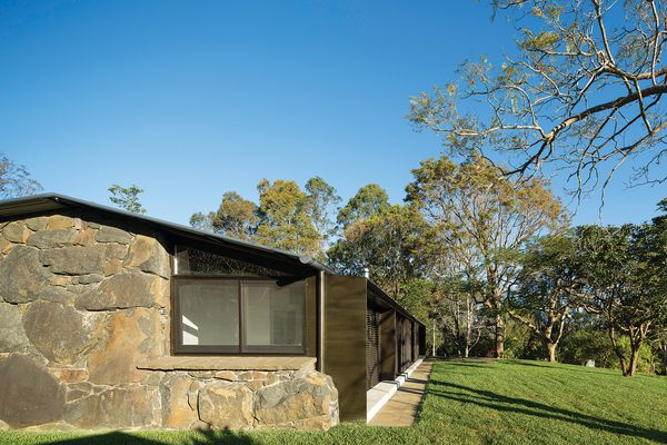 The shell of the house merges the existing stonework with the new frame, creating a clear relationship with the landscape beyond.