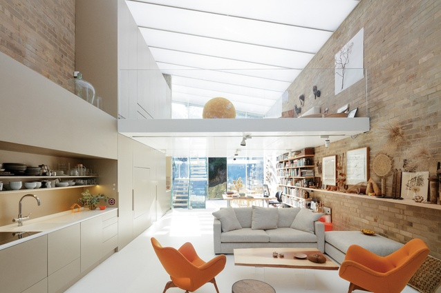 A mezzanine level hovering within the space is open to views of the landscape at both ends of the house.