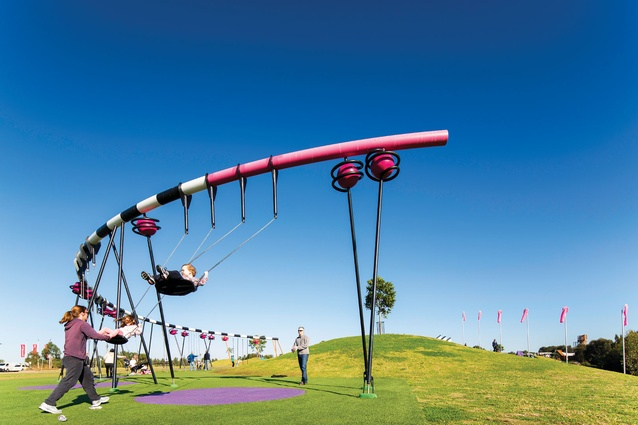 A Semicircular Swing Set Parallels The Nearby Grass Mound