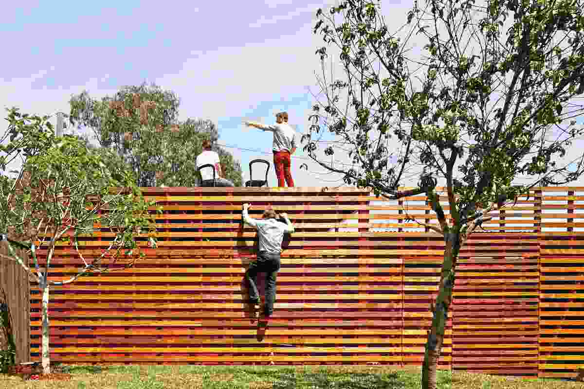 A lightweight timber-batten screen leads to a roof deck on the garage.