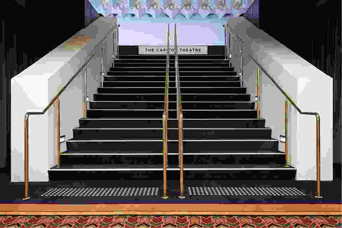An understated stair with dark carpet leads to the glittering theatre above.