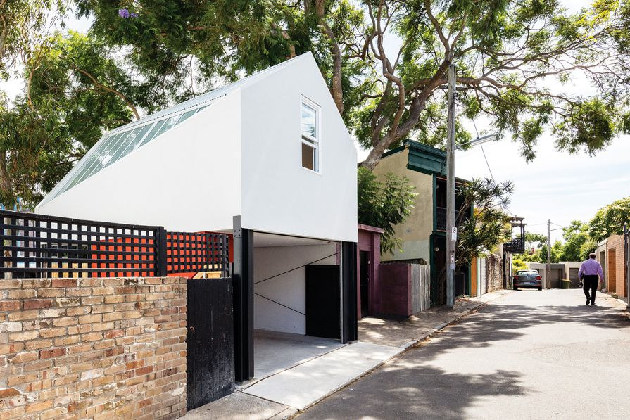 The studio presents a modest facade to the rear lane, but adopts a more playful form to address the existing house.