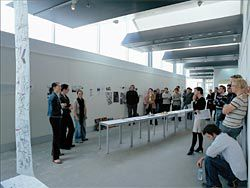 Exhibition space in the Kaurna Building with an architecture crit in progress.