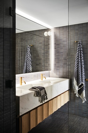 The juxtaposition of white marble and dark tiles lends the bathroom a quiet elegance.