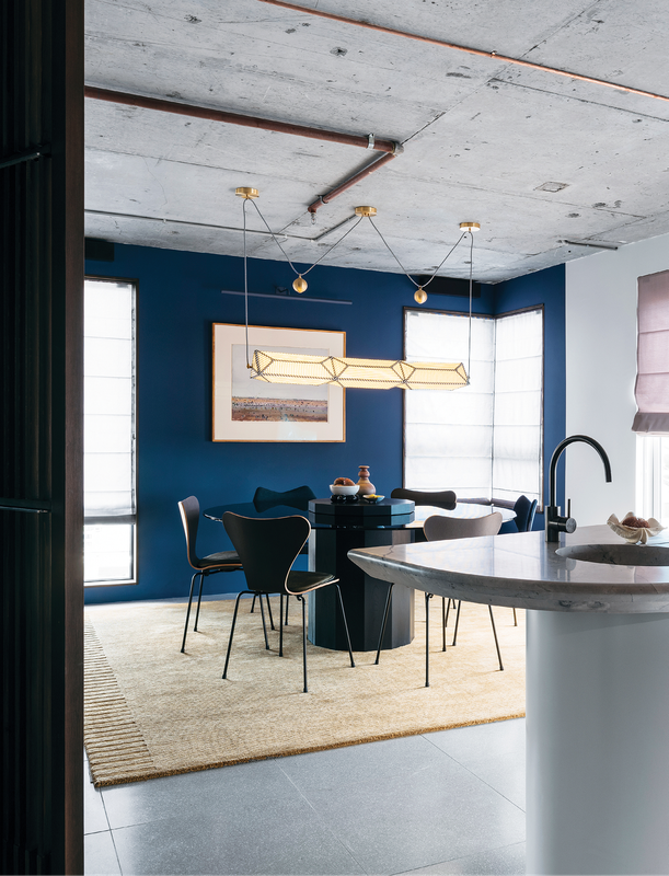 The view from the kitchen takes in the dining room's exposed concrete ceiling, a statement light fitting and royal blue walls. Artwork: Fred Williams.