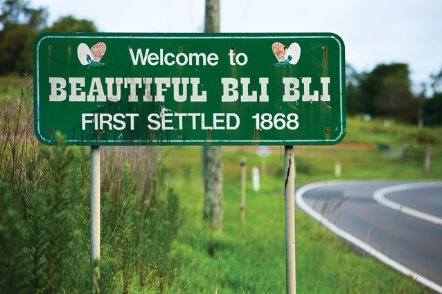 "The town sign for Bli Bli on Queensland's Sunshine Coast welcomes visitors to ""Beautiful Bli Bli, first settled 1868,"" in a message ornamented with butterflies."