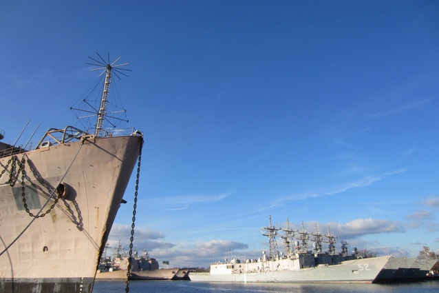 Retired naval vessels are moored at the shipyard.