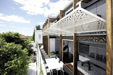The main living zones face the ideal northern aspect, with sliding walls and doors opening to an outdoor living garden shaded by perforated adjustable screens.