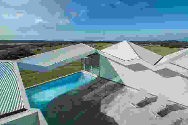 The central courtyard is open to the sky, while the roof folds over the pool as an open canopy.