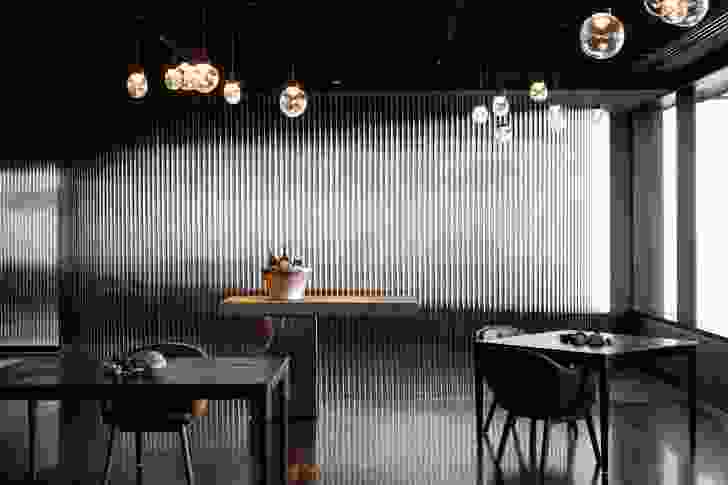 The dining room is silver and black and lit by hand-blown lights by Melbourne artist Emma Lashmar.