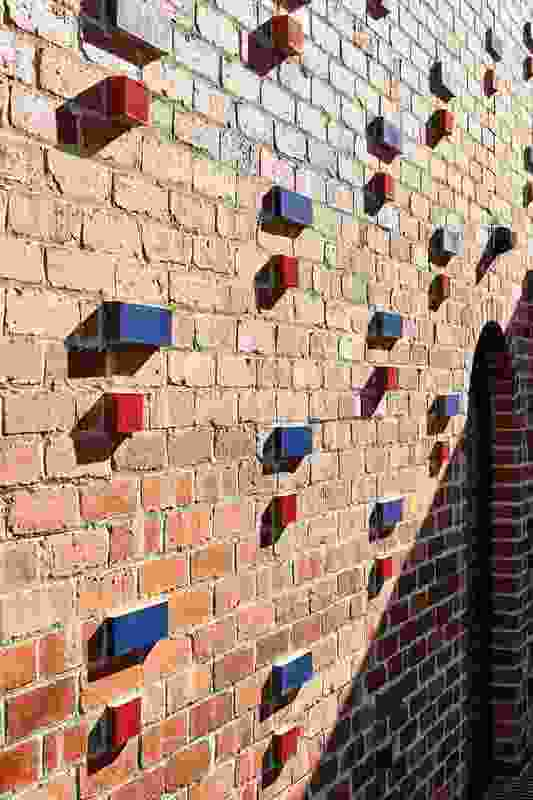 The red and blue brick accents provide a sense of playfulness and reduces the otherwise imposing nature of the brick wall.