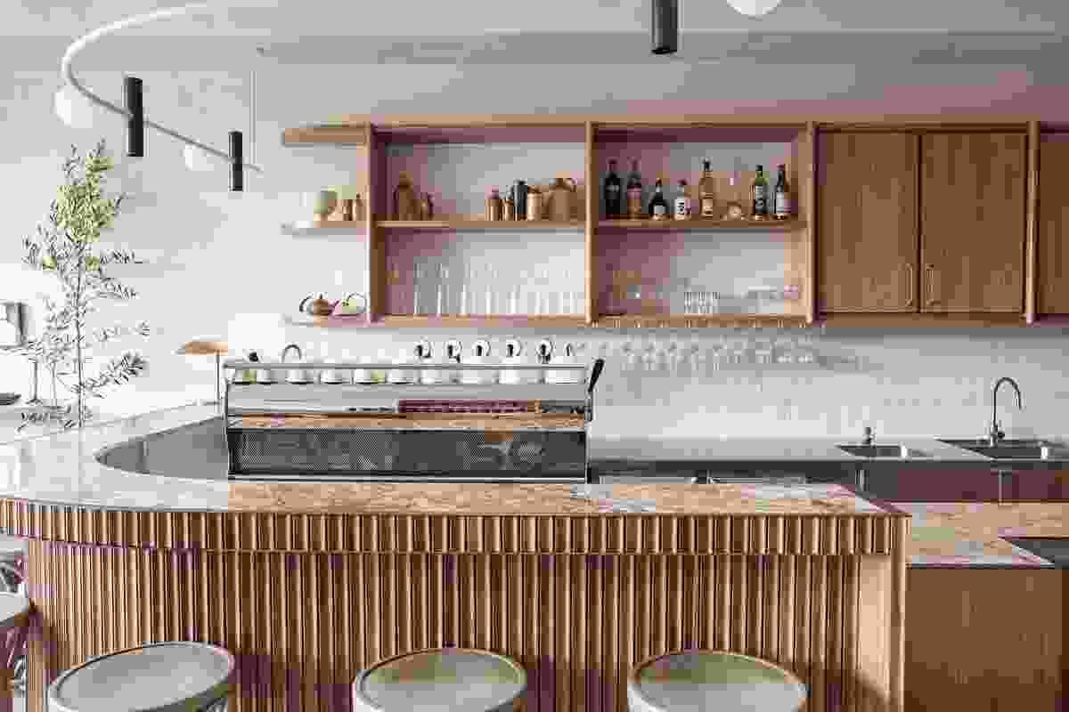 """大型弯曲的咖啡吧具有""""金色卡布奇诺""""大理石,黄铜装饰和凹槽木材镶板。"""