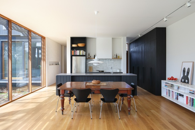 Kitchen joinery is in the same dark cladding as the external walls, while large windows capture views of the bush.