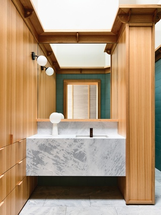 A marble vanity and stone floor tiles complement the lightness of the oiled timber lining boards.