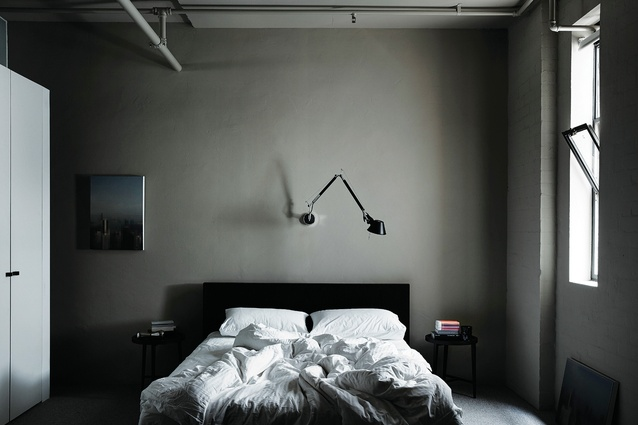 The bedroom borrows natural light via a lowered wall between it and the living area. Artwork: Chris Christodoulou.